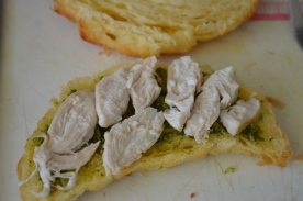 Layer some chicken over the pesto.